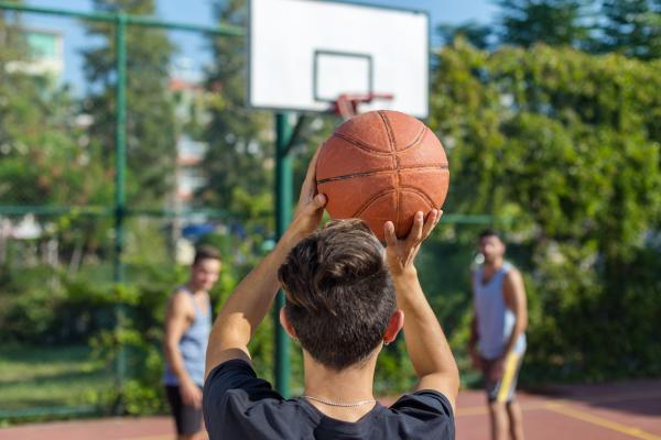 Back of young person's head preparing to shoot basketball at hoop with defence players in background