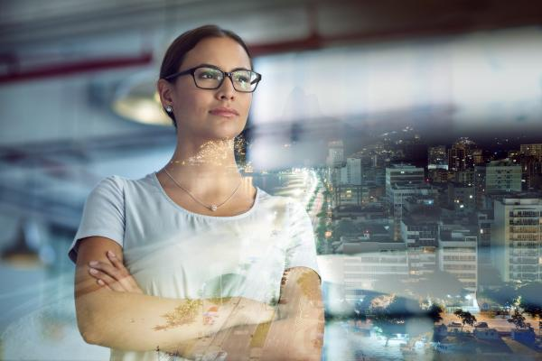 Businesswoman in glasses looks our over evening cityscape