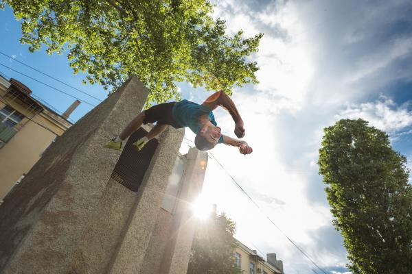 Talented parkour sportsperson doing backflip in urban setting